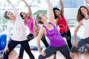 Smiling women exercising with arms raised while looking up