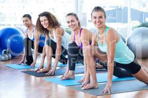 Fit women in fitness studio doing high lunge pose