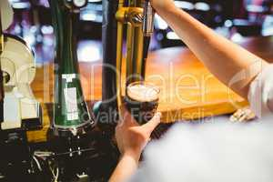 Barkeeper holding glass below beer dispenser tap
