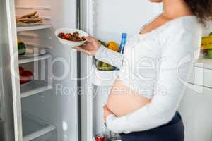 Pregnant woman keeping strawberries in fridge