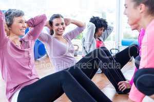 Women exercising on floor with hands behind head