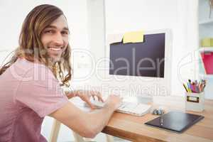 Portrait of happy hipster typing on keyboard in office