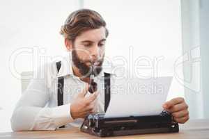 Hipster with smoking pipe working on typewriter