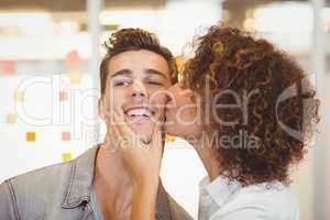 Woman with curly hair kissing businessman