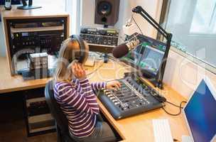 Female radio host operating sound mixer