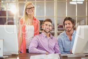 Stylish business people sitting by computer