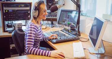 Female radio host broadcasting through microphone