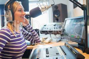 Happy female radio host broadcasting in studio
