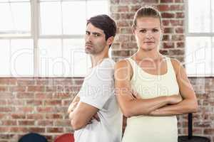 Fit couple with arms crossed in bright exercise room