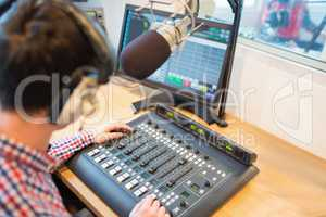 High angle view of radio host operating sound mixer