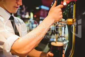 Bartender holding beer glass below dispenser tap