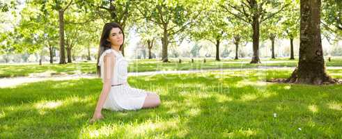 Young woman sitting on grassland in park