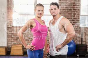 Standing muscular unsmilling couple facing the camera