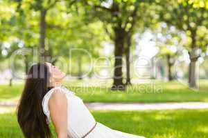 Side view of brown hair woman sitting on grass