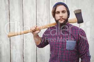 Hipster holding axe on shoulder