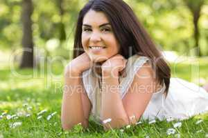 Portrait of pretty cheerful woman lying on grassland