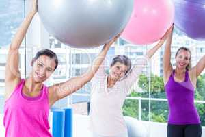 Portrait of happy women holding exercise balls with arms raised
