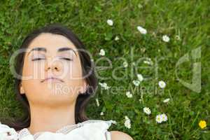 Beautiful young woman relaxing on grassland