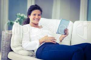 Portrait of happy woman reclining on sofa with tablet