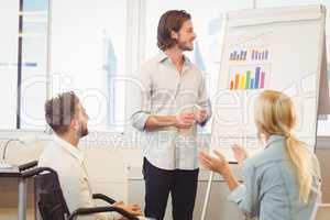 Business people with male colleague looking at multi colored gra