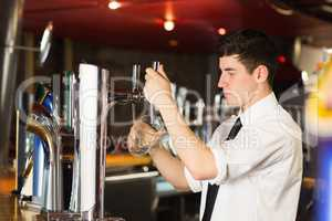 Barkeeper holding glass in front of beer dispenser at bar