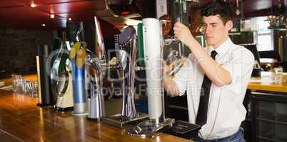 Barkeeper holding glass in front of beer dispenser