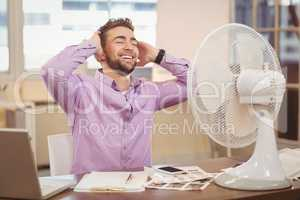 Relax businessman sitting by electric fan