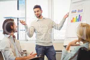 Confident businessman giving presentation in meeting room