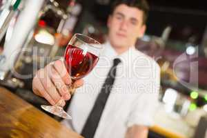 Male barkeepe serving alcohol