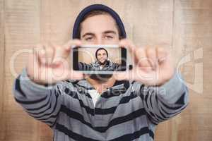 Hipster with hooded shirt taking self portrait