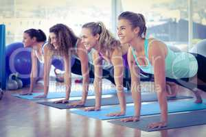 Women smiling while doing plank pose in fitness center