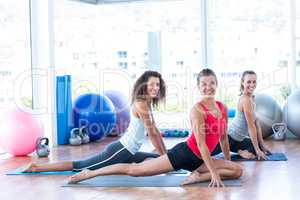 Women smiling while doing pigeon pose