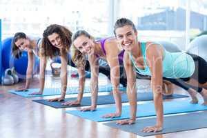 Cheerful women doing plank pose in fitness studio