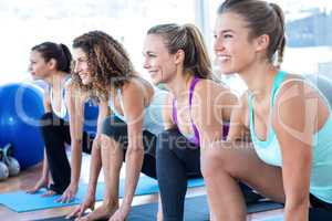 Cheerful woman in fitness studio doing lunge pose