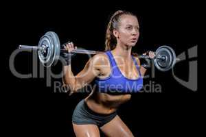 Sporty female bodybuilder lifting crossfit
