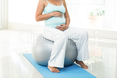 Pregnant woman sitting on exercise ball touching her belly