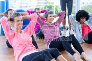 Attractive women doing sit ups on hardwood floor