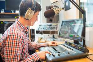 Radio host using sound mixer in studio