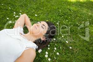 Woman relaxing with hand behind head on grassland