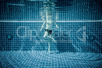 Persons standing under water in a swimming pool