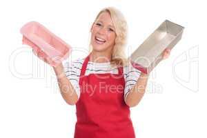 Hausfrau in Küchenschürze zeigt verschiedene Backformen