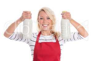 Hausfrau in Schürze hält zwei Flaschen Milch