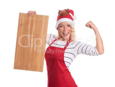 Weihnachtsfrau in Schürze hält ein Holzbrett als Werbefläche