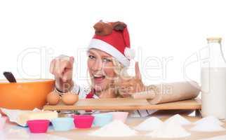 Weihnachtsfrau mit Backutensilien zeigt Daumen hoch
