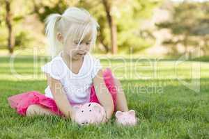 Little Girl Having Fun with Her Piggy Banks Outside