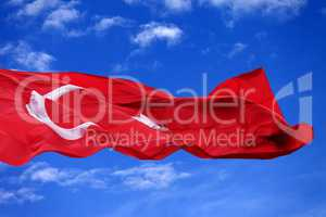 Waving flag of Turkey against blue sky