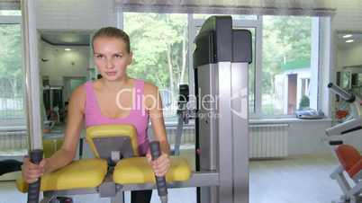 Health fitness club interior woman working out on leg curl machine