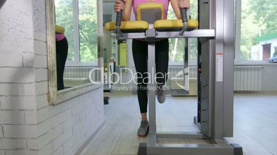 Fit young woman training in health fitness club on standing leg curl machine