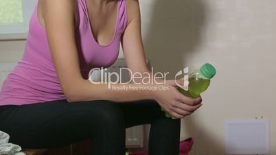 Fit young woman drinking energy drink from bottle in fitness club locker room