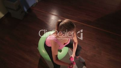 JIB CRANE: Fit woman exercising on fitness ball with light dumbbells in gym